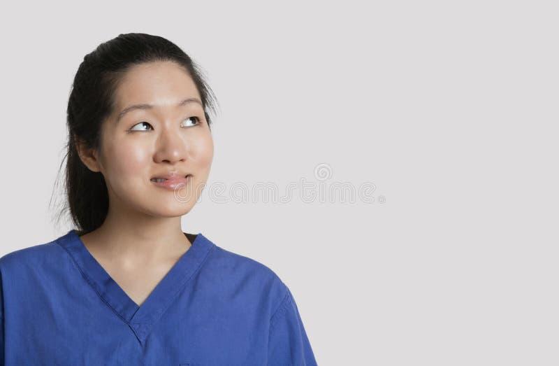Doutor fêmea asiático novo que olha acima sobre o fundo cinzento foto de stock