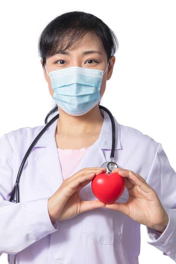 Doutor fêmea asiático que guarda o coração vermelho com estetoscópio fotografia de stock royalty free