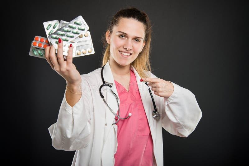 Doutor fêmea atrativo que aponta as bolhas com tabuletas foto de stock royalty free