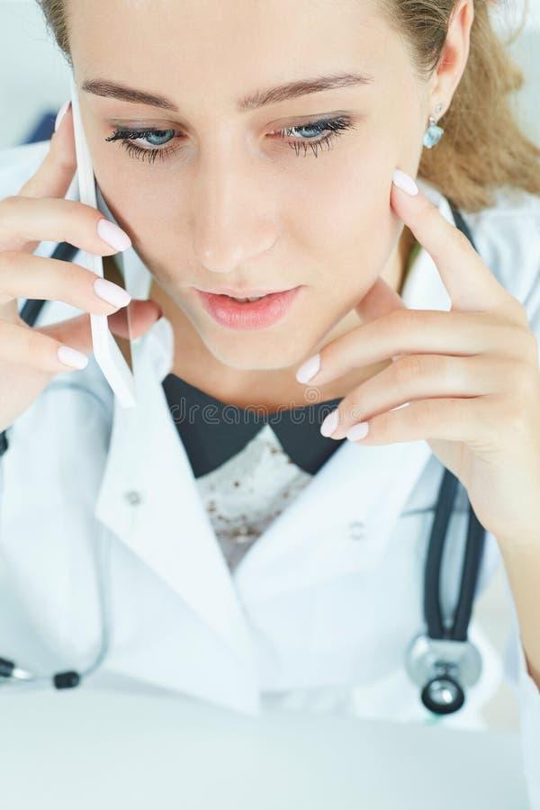 Doutor fêmea atrativo seguro novo que fala no telefone com paciente Vista superior Conceito remoto dos cuidados médicos imagens de stock