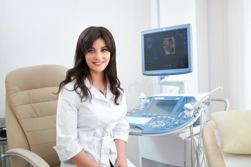 Doutor fêmea bonito que senta-se em seu escritório perto do sc do ultrassom fotos de stock royalty free