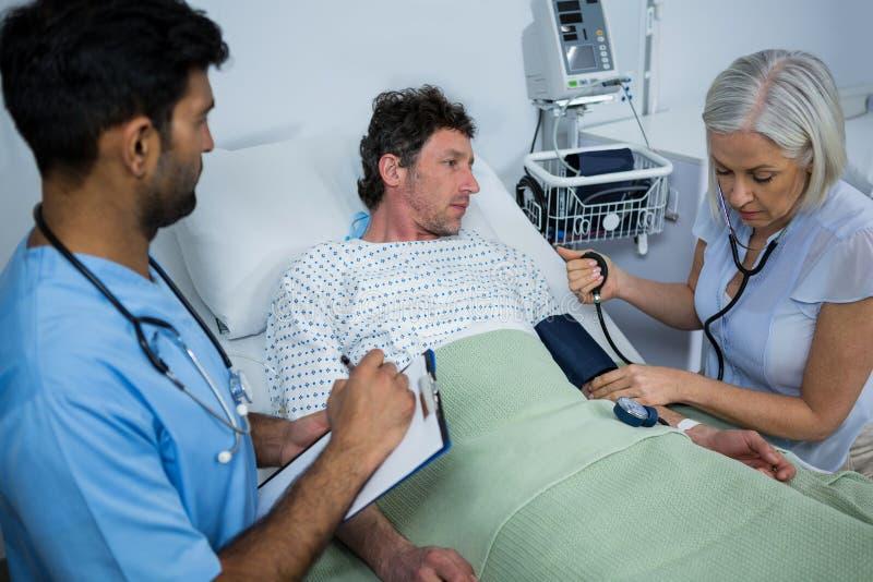 Doutor fêmea Checking Blood Pressure do paciente imagens de stock