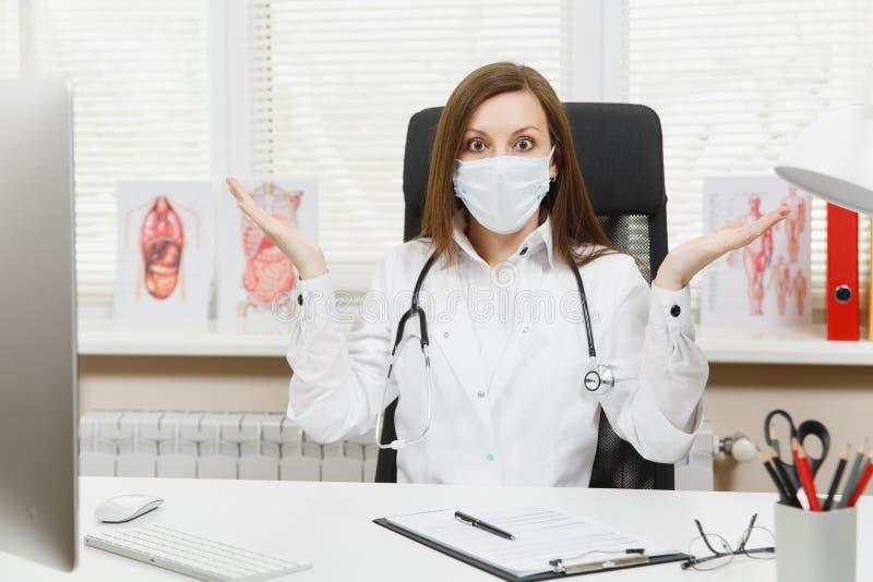 Doutor fêmea chocado jovens que senta-se nas mãos de espalhamento da mesa que trabalham com documentos médicos no escritório clar fotos de stock