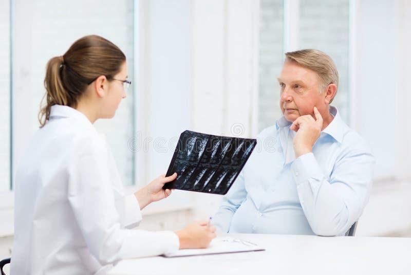 Doutor Fêmea Com O Ancião Que Olha O Raio X Foto de Stock
