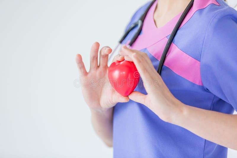 Doutor fêmea com o estetoscópio que guarda o coração vermelho, isolado no wh fotos de stock royalty free