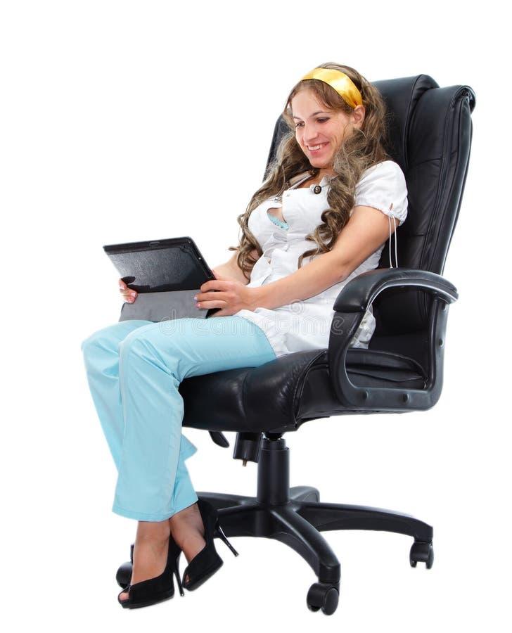 Doutor fêmea de sorriso com o tablet pc que senta-se na poltrona fotografia de stock