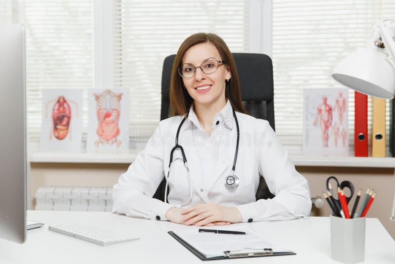 Doutor fêmea de sorriso dos jovens que senta-se na mesa, trabalhando no computador com originais médicos no escritório claro no h imagens de stock royalty free