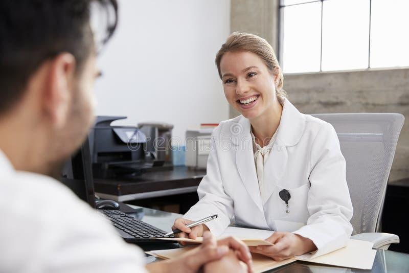 Doutor fêmea de sorriso em consulta com o paciente masculino fotografia de stock