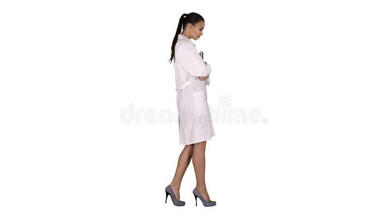 Doutor fêmea de sorriso feliz que anda guardando cadernos ou documentos no fundo branco fotografia de stock