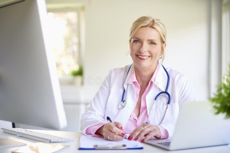 Doutor fêmea de sorriso no trabalho fotografia de stock royalty free