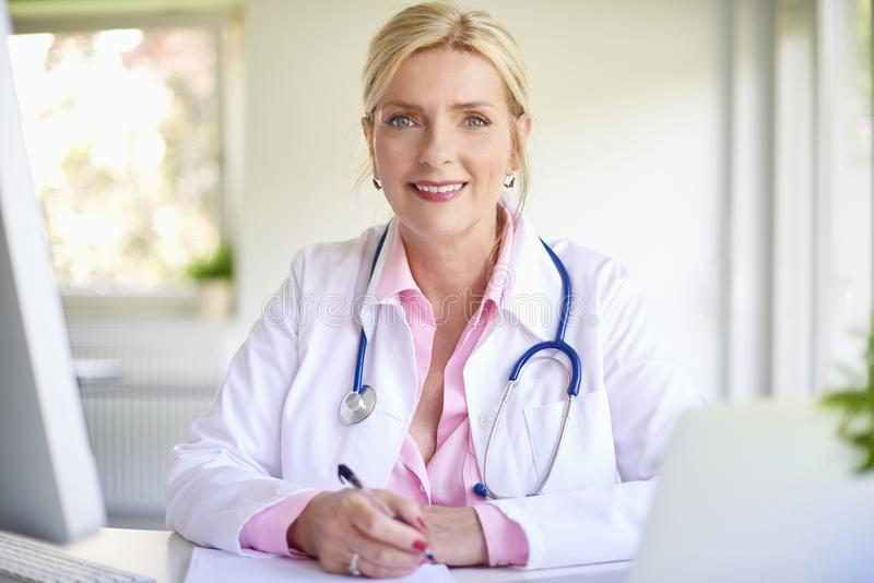 Doutor fêmea de sorriso no trabalho fotografia de stock