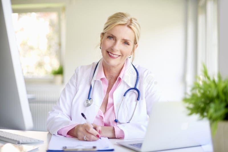 Doutor fêmea de sorriso no trabalho imagem de stock royalty free
