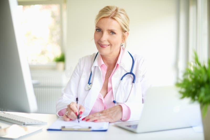 Doutor fêmea de sorriso no trabalho imagem de stock