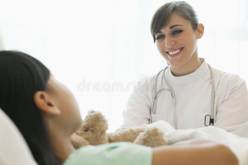 Doutor fêmea de sorriso que fala ao paciente da menina que encontra-se para baixo em uma cama de hospital imagens de stock royalty free