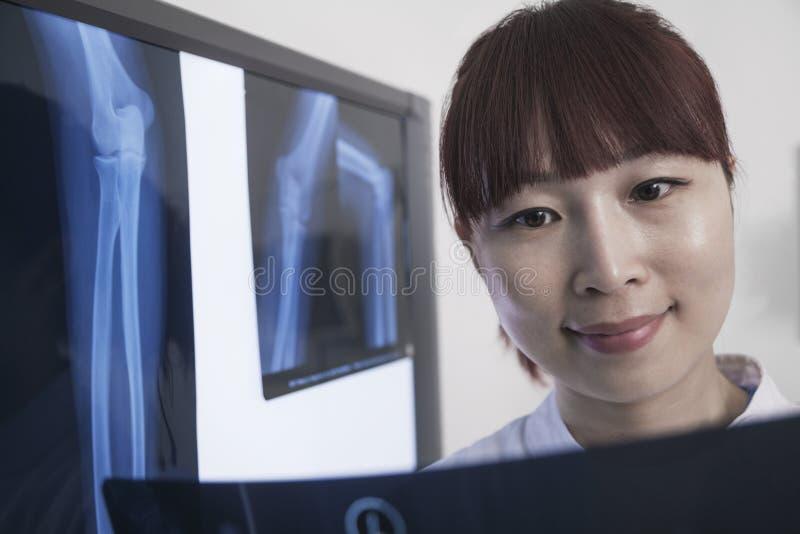 Doutor fêmea de sorriso que olha o raio X dos ossos humanos imagem de stock royalty free