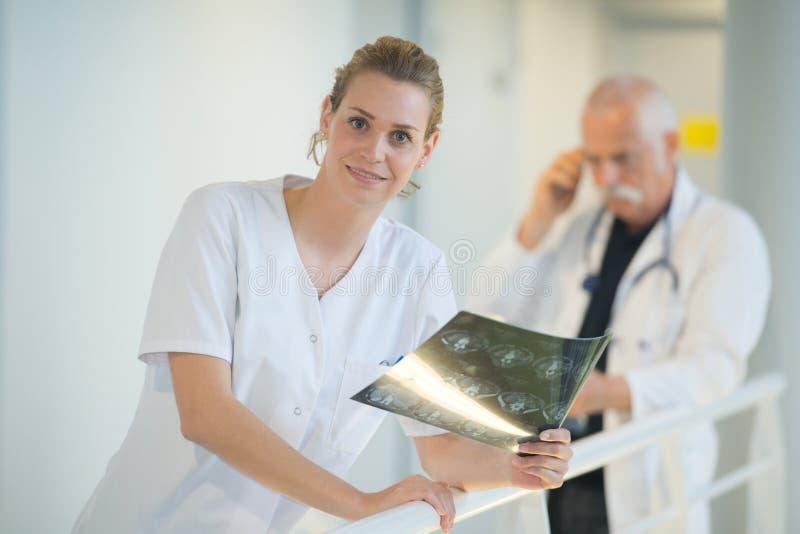 Doutor fêmea de sorriso que olha o raio X no corredor do hospital fotos de stock