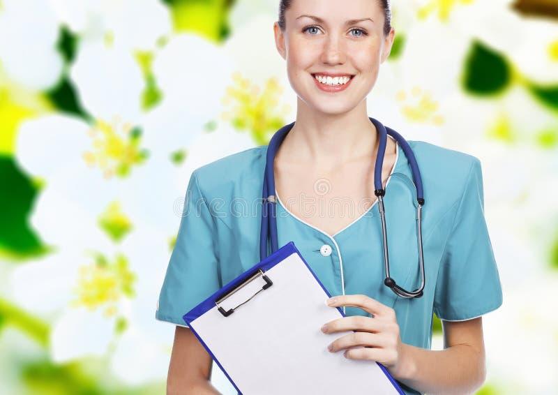 Doutor fêmea de sorriso que prende uma prancheta fotos de stock