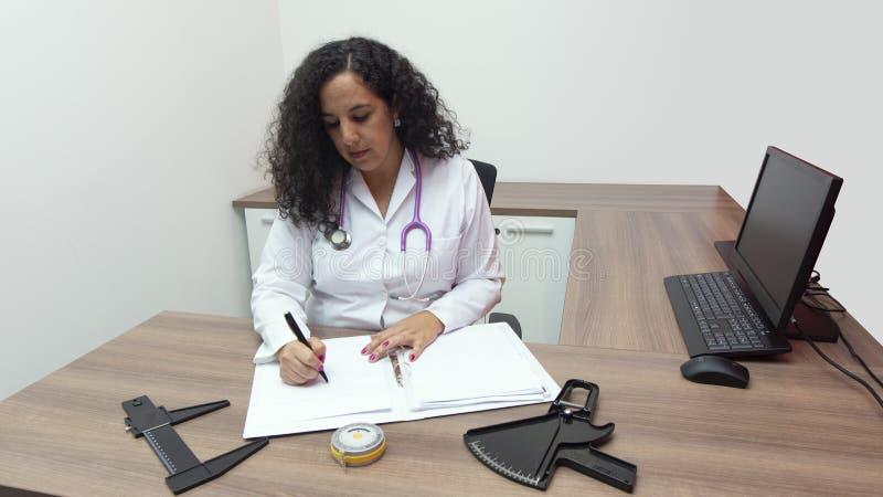 Doutor fêmea do latino fêmea que senta-se com atitude séria em seu escritório com o estetoscópio em seu pescoço que escreve em se imagens de stock royalty free