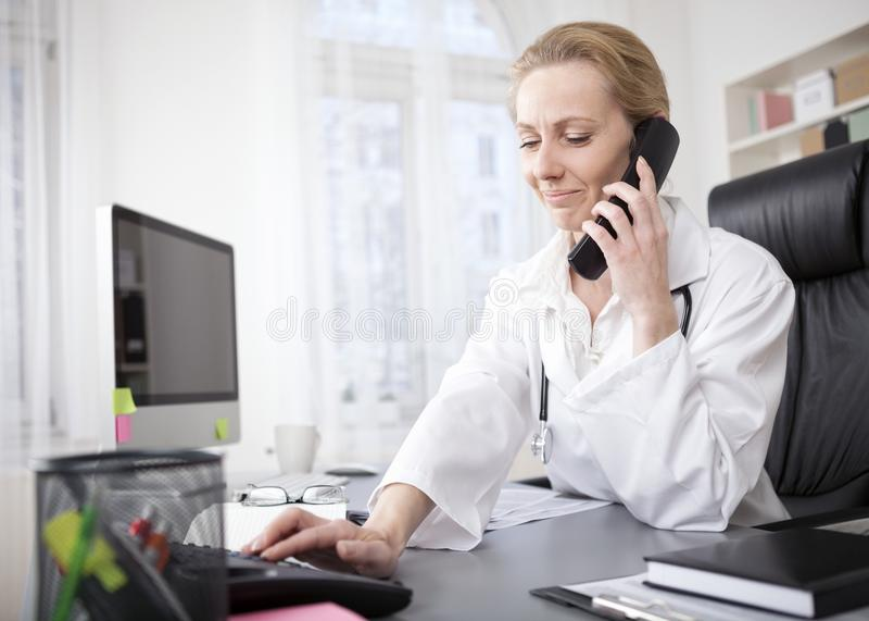 Doutor fêmea em seu escritório que disca um telefone foto de stock royalty free