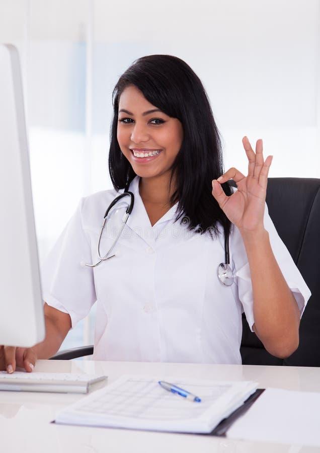 Doutor fêmea feliz Gesturing Ok Sign fotografia de stock royalty free