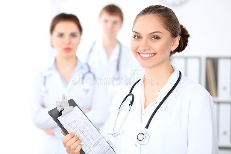 Doutor fêmea feliz que mantém a prancheta médica quando o pessoal médico estiver no fundo fotografia de stock royalty free