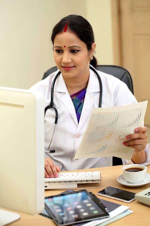 Doutor fêmea indiano novo que verifica originais pacientes imagem de stock