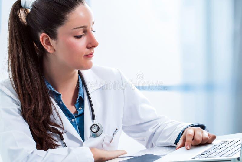 Doutor fêmea médico que revê resultados no portátil fotografia de stock