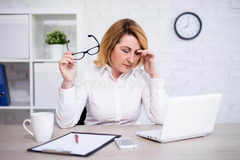 Doutor fêmea maduro forçado ou cansado que senta-se no escritório moderno fotografia de stock royalty free