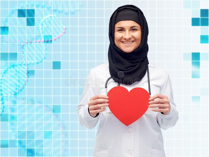 Doutor fêmea muçulmano no hijab que guarda o coração vermelho fotografia de stock royalty free