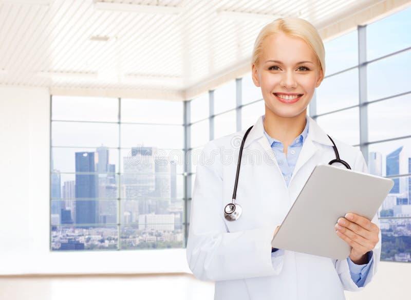 Doutor fêmea novo de sorriso no revestimento branco foto de stock