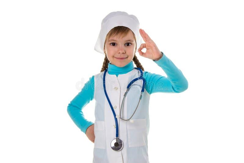Doutor fêmea novo de sorriso que veste o sinal da aprovação da exibição do estetoscópio com os dedos, guardando um outro braço na fotografia de stock