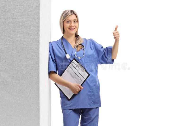 Doutor fêmea novo em um uniforme azul que inclina-se contra a parede e que faz um polegar acima do sinal fotos de stock royalty free
