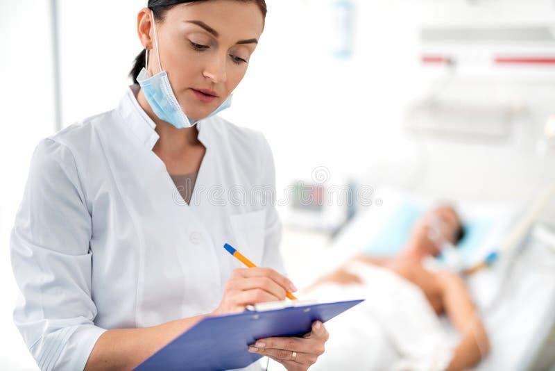 Doutor fêmea novo que enche-se acima do formulário médico imagens de stock royalty free