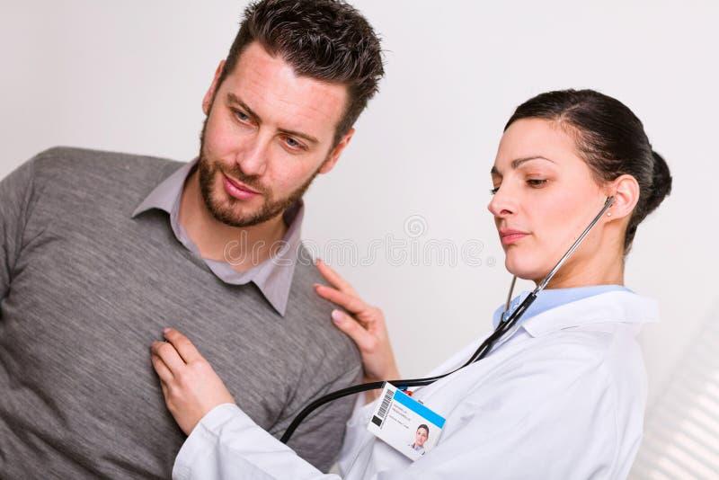 Doutor fêmea novo que escuta uma pulsação do coração foto de stock