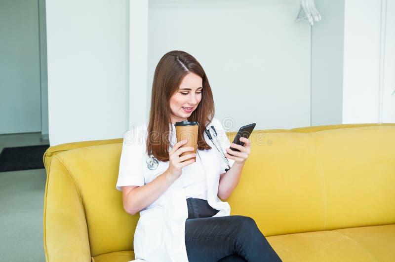 Doutor fêmea novo que senta-se no sofá amarelo no centro médico com telefone celular e café bebendo durante sua ruptura Estudante imagens de stock royalty free