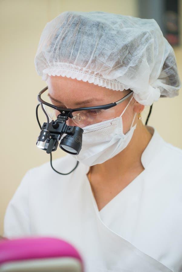 Doutor fêmea novo que veste os binóculos dentais da lupa, retrato do headshot no processo do trabalho fotografia de stock royalty free