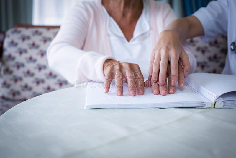 Doutor fêmea que ajuda um paciente cego em ler o livro do braile fotos de stock
