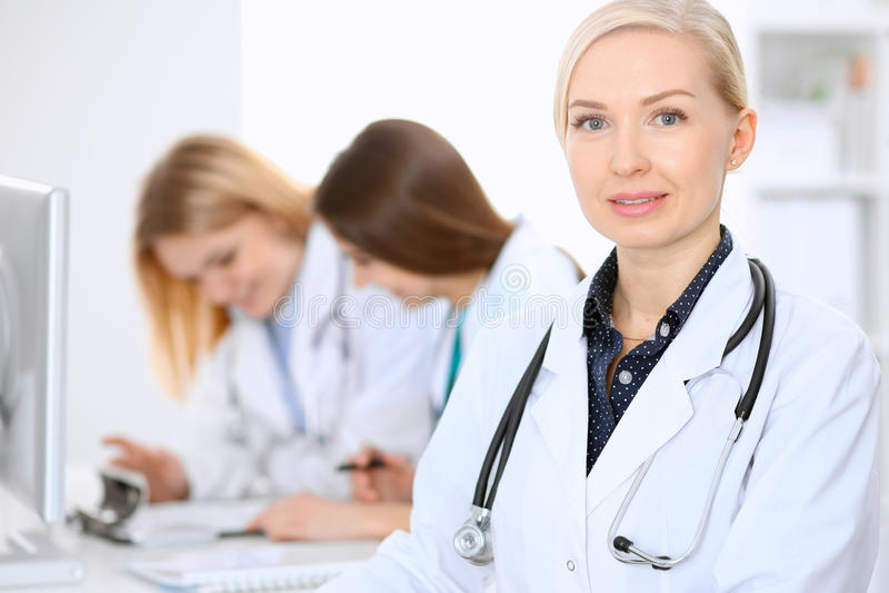 Doutor fêmea que conduz uma equipa médica no hospital fotografia de stock