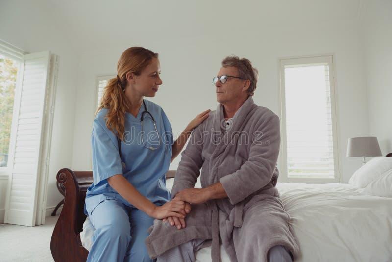 Doutor fêmea que consola o homem superior ativo na cama no quarto na casa confortável fotografia de stock royalty free
