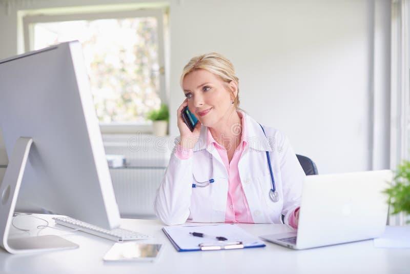 Doutor fêmea que consulta com seu paciente no telefone celular fotografia de stock