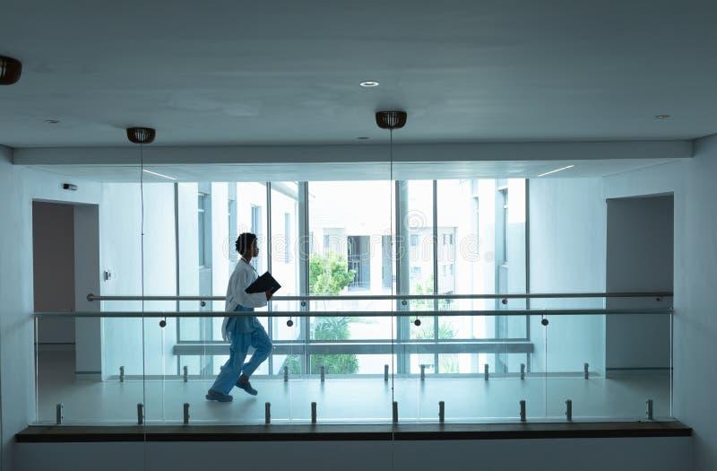 Doutor fêmea que corre no corredor no hospital foto de stock
