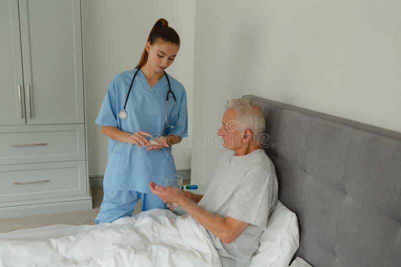 Doutor fêmea que dá a medicina ao paciente superior ativo no quarto imagem de stock