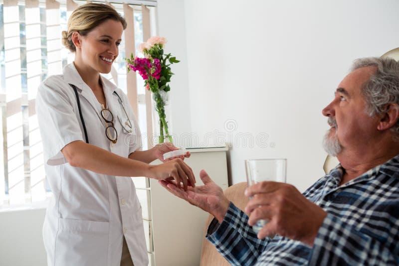 Doutor fêmea que dá medicinas ao paciente superior fotos de stock