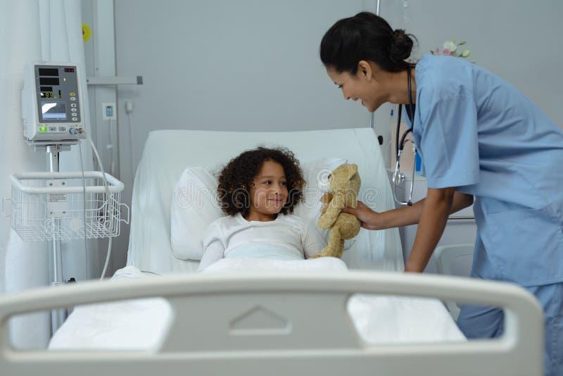 Doutor fêmea que dá o urso de peluche ao paciente da criança na divisão foto de stock royalty free