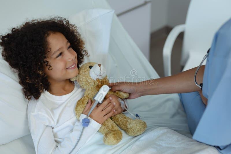 Doutor fêmea que dá o urso de peluche ao paciente da criança na divisão imagens de stock royalty free