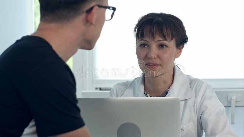 Doutor fêmea que discute o diagnóstico com o paciente masculino em seu escritório fotos de stock royalty free