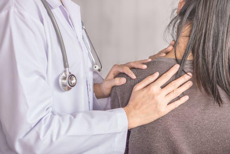 Doutor fêmea que examina um sofrimento paciente da dor do pescoço e do ombro foto de stock