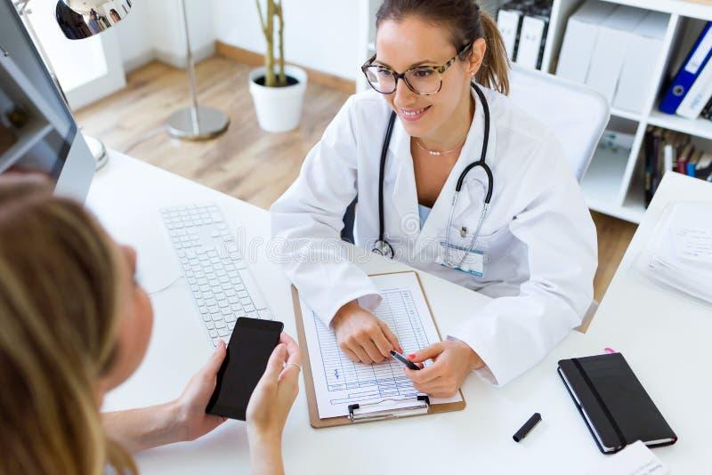 Doutor fêmea que explica o diagnóstico a seu paciente foto de stock