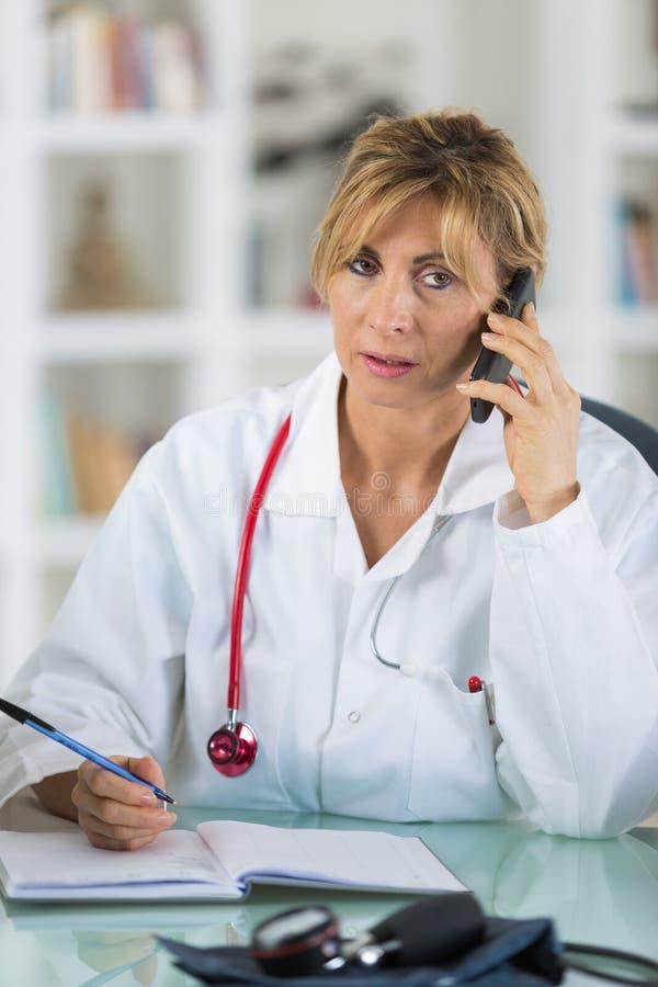 Doutor fêmea que fala no telefone no centro diagnóstico fotografia de stock royalty free