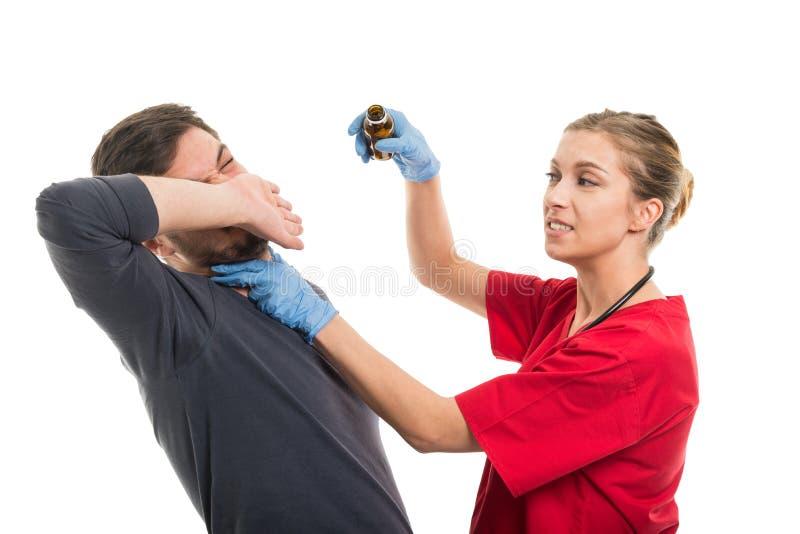 Doutor fêmea que força o paciente masculino que toma o xarope fotografia de stock royalty free